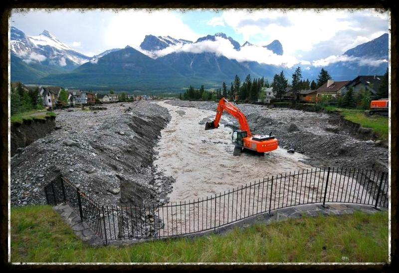 Backhoe's at work to save home on the banks of Cougar Creek