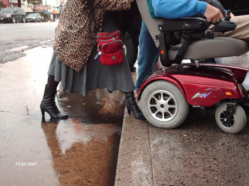 Motorized Wheelchair Struggles to Climb Steep Sidewalk