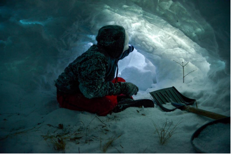 A student sits inside the traditional quinsy snow shelter they helped to build.