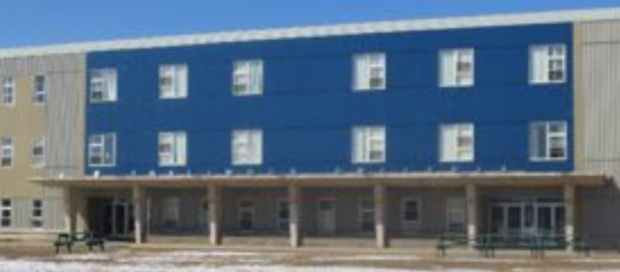 Photo of the blue and white_ three-storey J.R. Smallwood Middle School in Wabush owned by Cliffs Mining Company.
