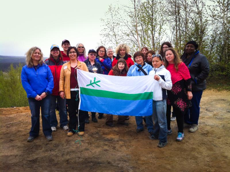 Women of Building Links hold up the Labrador Flag near Muskrat Falls.