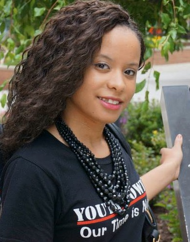 Pauline with long flowing hair, beaded black neckllace and YOUTH POWER! Our Time is Now shirt