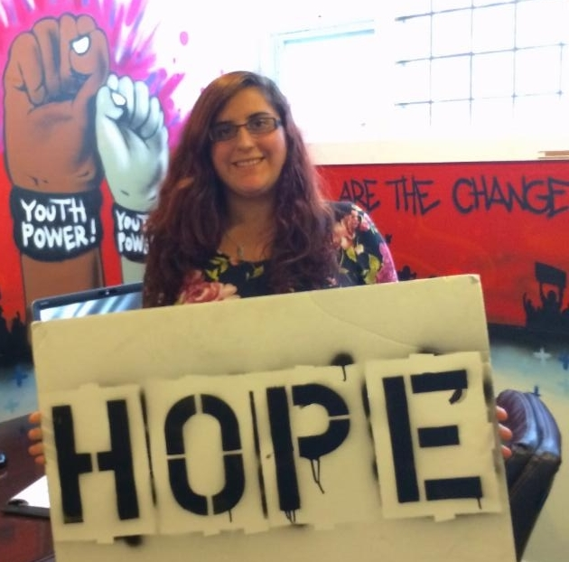 Brianna holding the Hope Board in front of the YP! mural of fists with the YOUTH POWER! wristband
