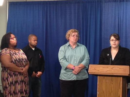 Stephanie Orlando Stands at podium speaking.  Another speaker and several YP! members stand at her side.