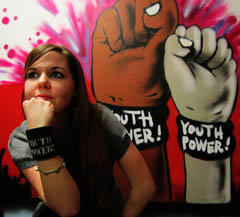 Ryanna (long brown hair) with YP! wristband on in front of painting of fists with YP! wristband on