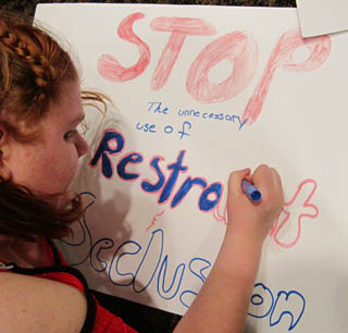 Girl draws poster that says stop the unnecessary use of restraint and seclusion