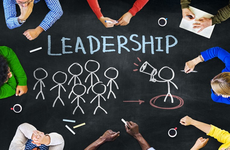 image of young people in a circle with stick figure people and leadership written in chalk in the center