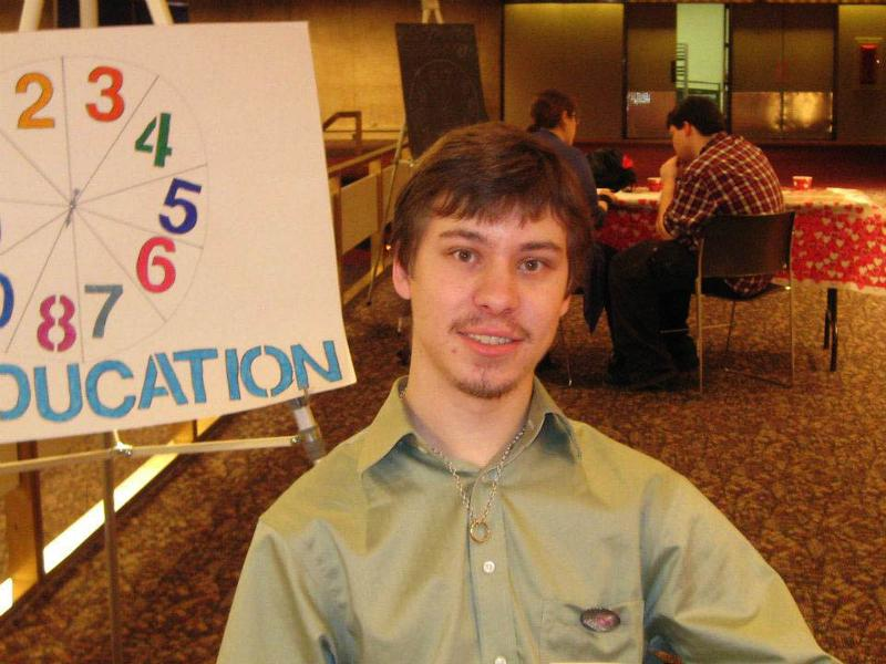 Curtis Grupe at legislative lunch 2012 in front of the education trivia wheel.