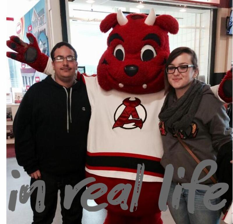 Alex and Christina with the Albany Devil Dog Mascot and In Real Life written across the bottom.
