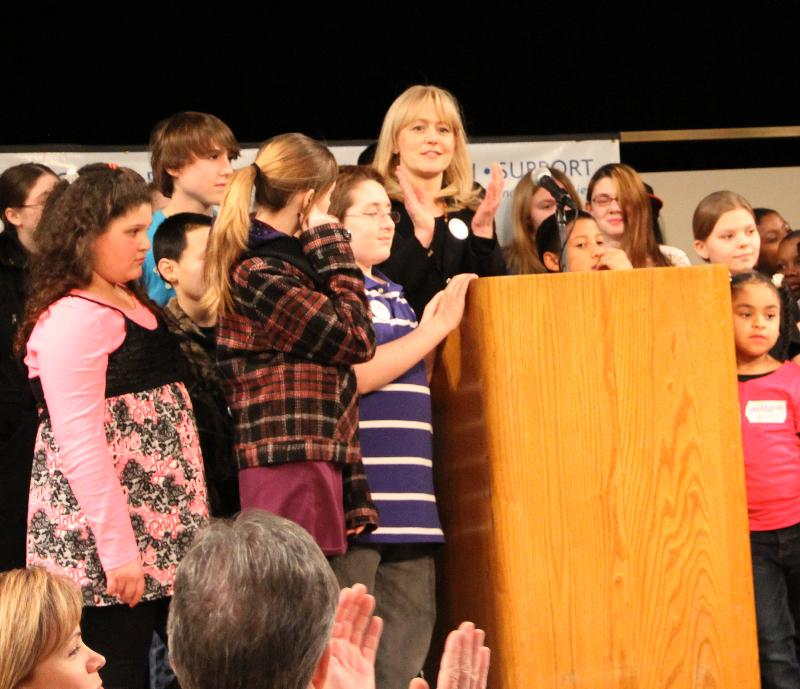 Kristin stands at the podium surrounded by children at the FTNYS legislative Lunch