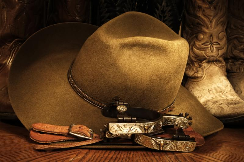 Cowboy or western themed image of a cowboy hat, fancy spurs, spur leathers and cowboy boots on a wood grained surface.
