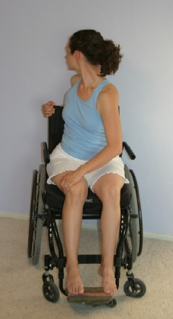 A woman holds a yoga pose in her wheelchair.