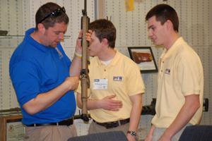 Engineering students examine a rifle