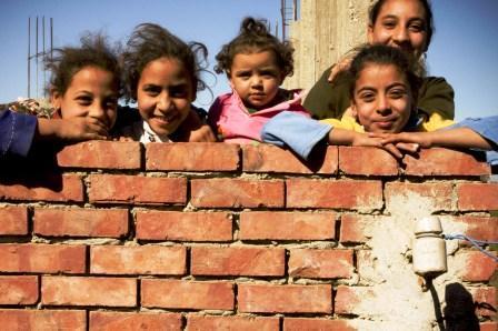 Smiling children behind brick wall