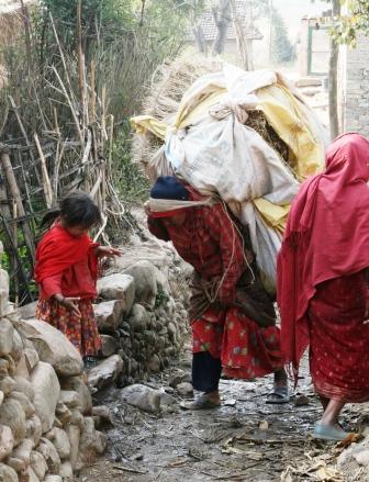 Village woman bearing huge load of wheat.