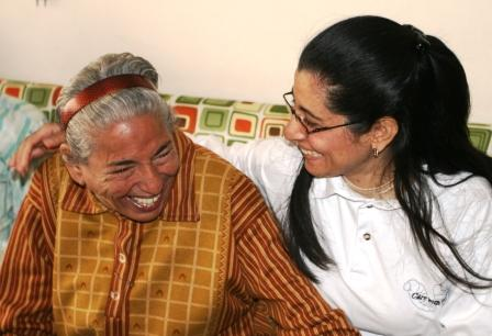 Caregiver smiling with elderly woman