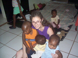 Nora on the floor with Haitian kids