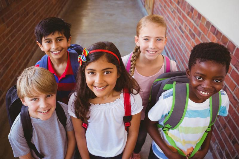 Portrait of smiling little school kids in school corridor