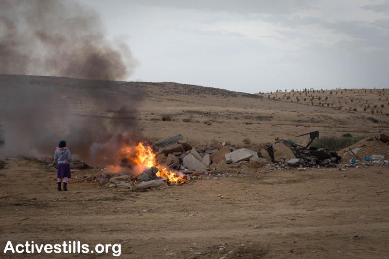 Bedouin girl watches as debris from her home burns-Al-Arakib