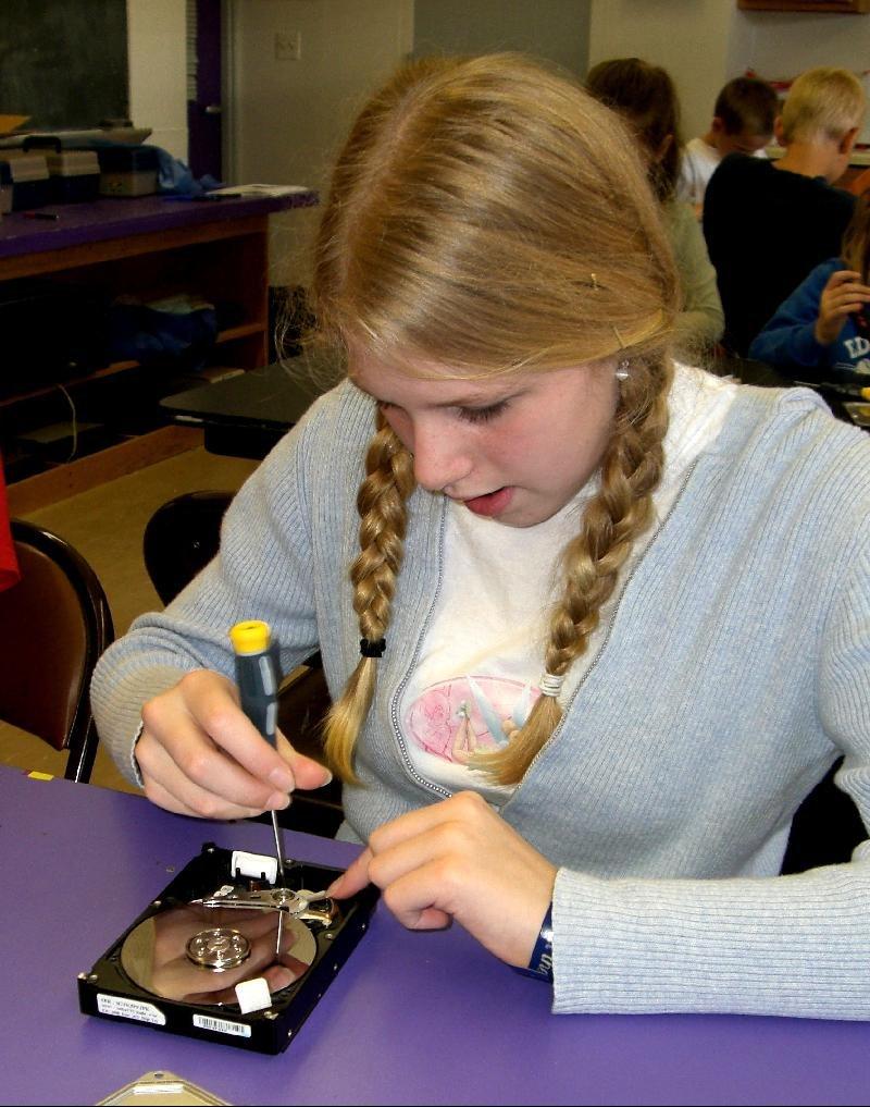 girl taking apart disk drive