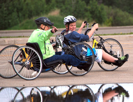 Dale Williams teaches 14-year-old Dylan Lawrance how to maneuver a hand cycle during the volunteer training session at the Centre 2000 parking lot Saturday, June 8, 2013. Lawrance decided to join the training session to learn how to ride handcycle and to teach others during the handcycling clinic taking place at Centre 2000 on Sunday. JOCELYN TURNER/DAILY HERALD-TRIBUNE