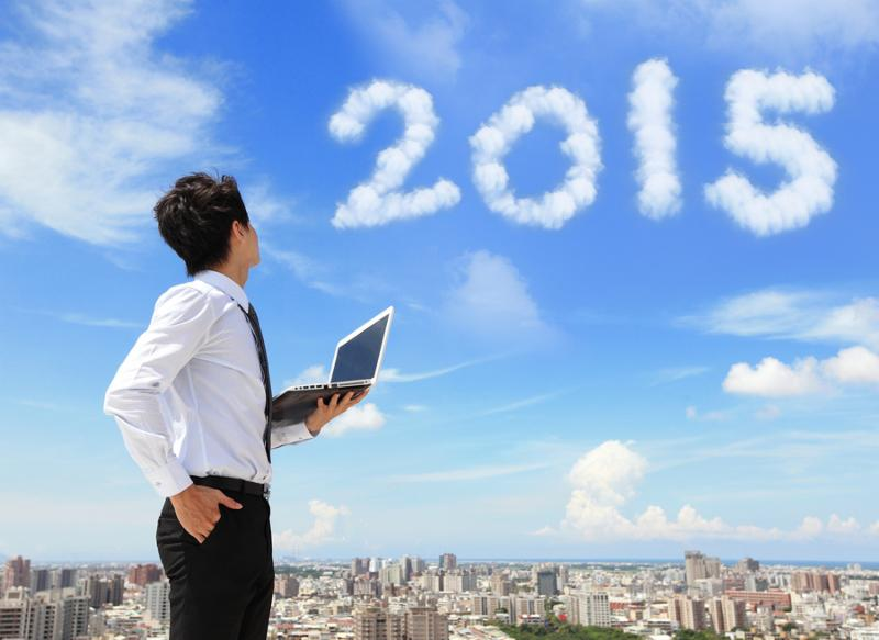 Young business man using laptop and look to 2015 year text with blue sky and cloud and cityscape in the background asian