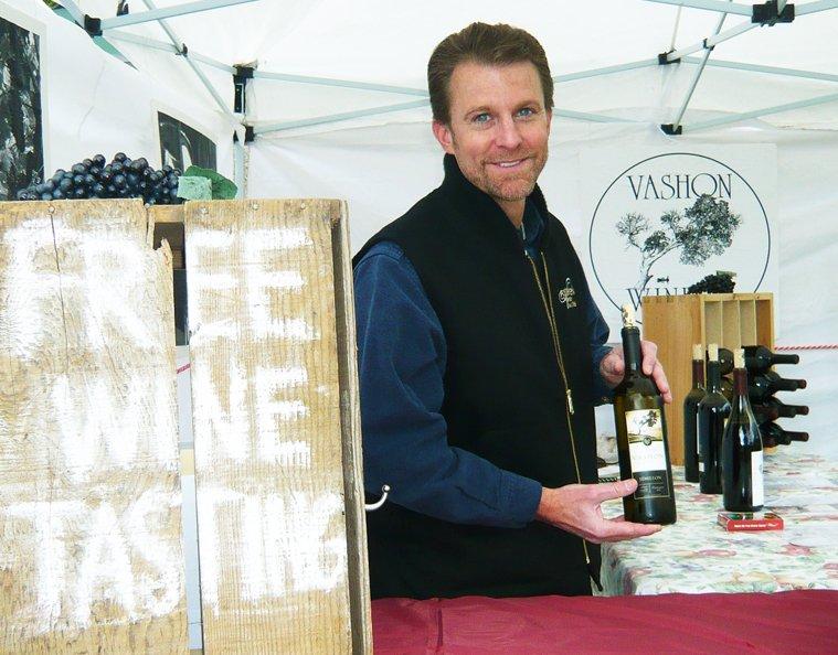 A Vashon Winery employee offers wine tasting at the Vashon Farmers Market.