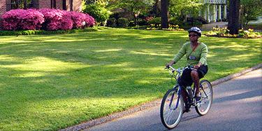 lady bicycling in nice neighborhood
