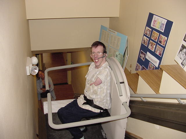 Arc staff demonstrating the wheelchair stair lift