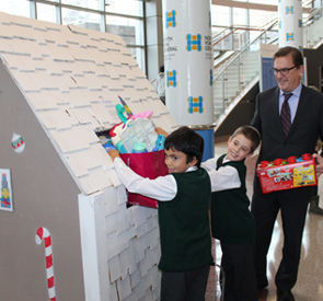 With the help of President and CEO Tim Rutledge, students Riyan Kassam and Jack Carlson donate gifts to the NYGH Toy Drive in 2014.