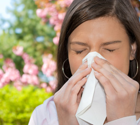 Woman sneezing because of her allergies.