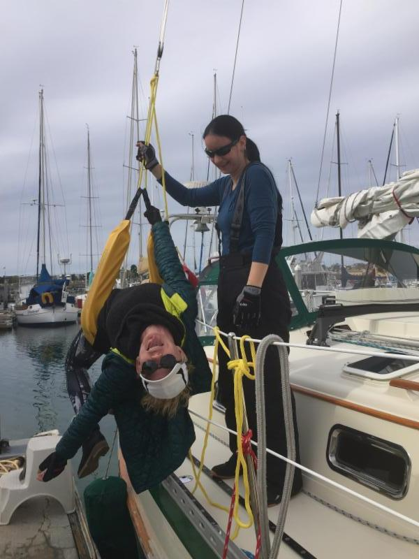 Mora Thompson, in life sling and Anita Losza practicing Woman Overboard Drills aboard Diane Berol's Celtic Song.
