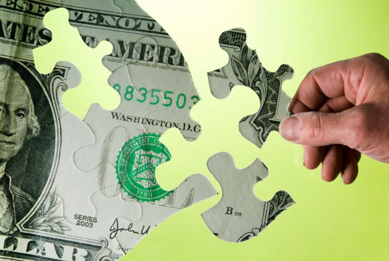 Picture of a hand putting together a puzzle with the image of dollar bill on it