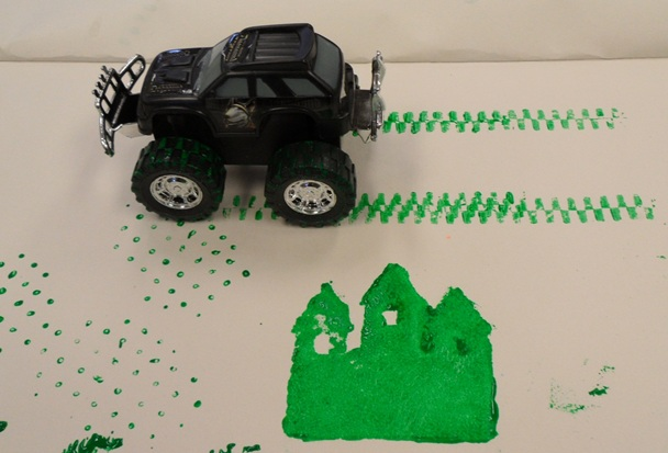 Photo showing a remote controlled toy car painting tracks across paper.