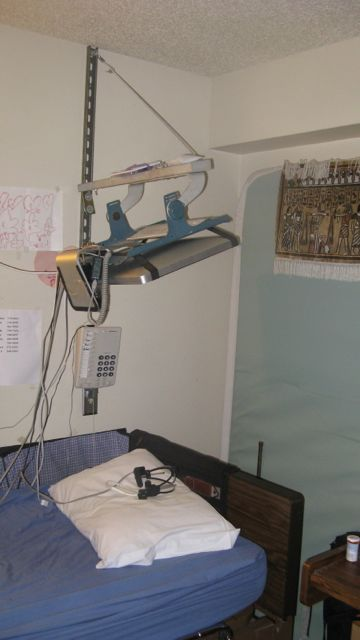 Photo of a computer wall-mounting system that adjusts for height and allows user to lay flat in bed.