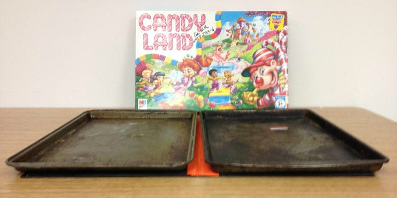 Photo of two cookie sheets on top of a Candy Land game board with the box top behind them.