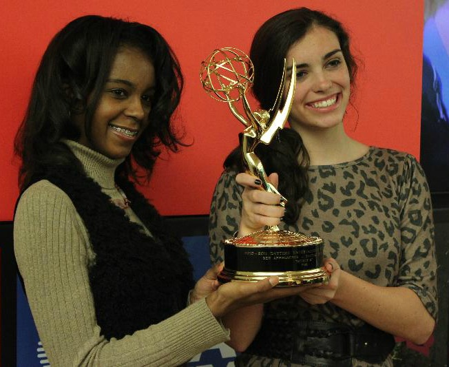 Two SciGirls holding an Emmy