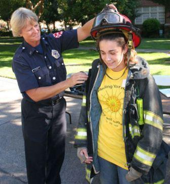 firefighter putting helmet on girl
