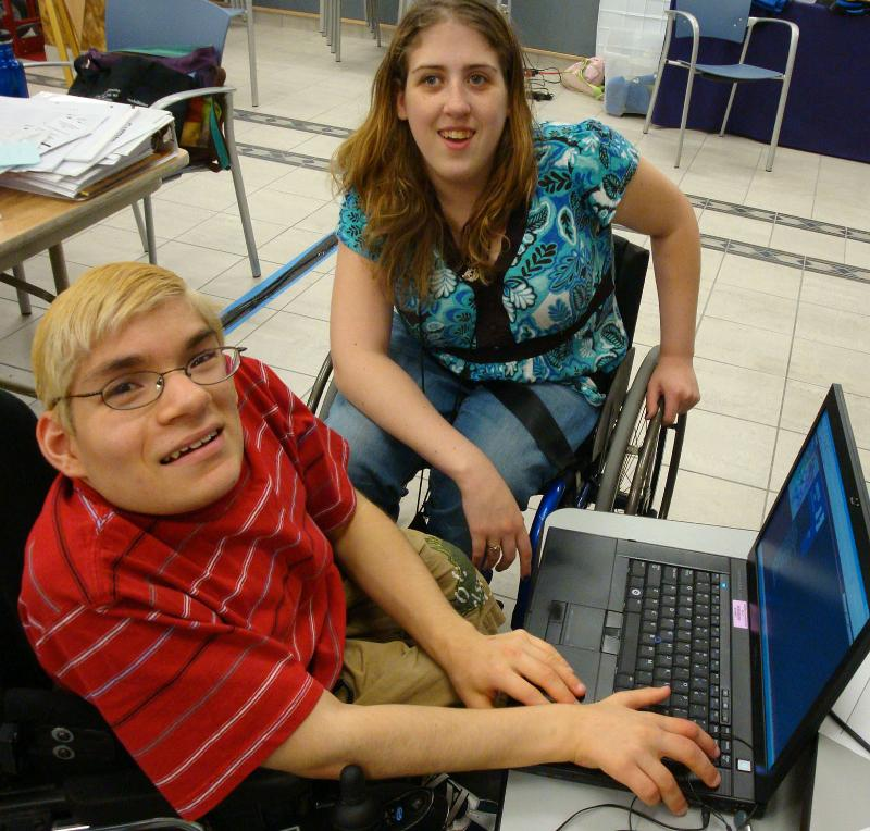 Boy and Girl in wheelchairs at laptop computer.