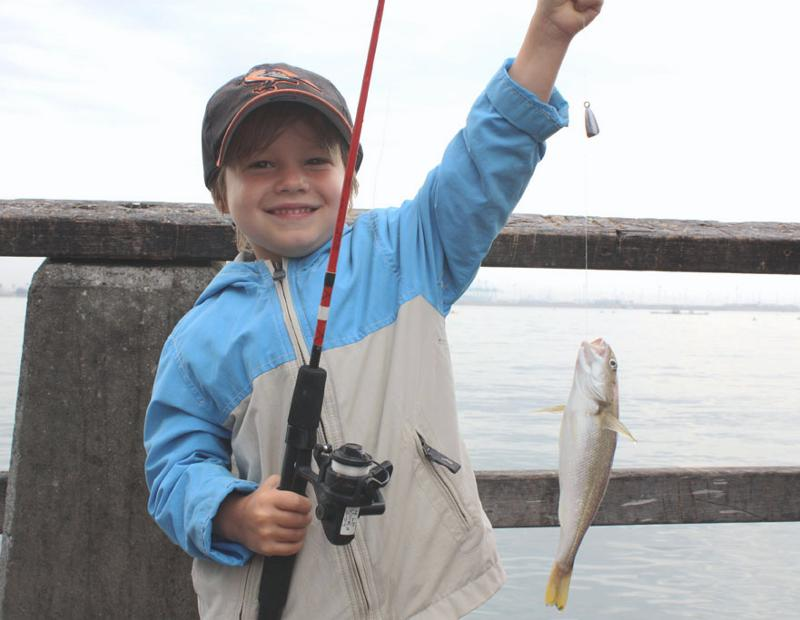 kid catching a fish on cabrillo pier