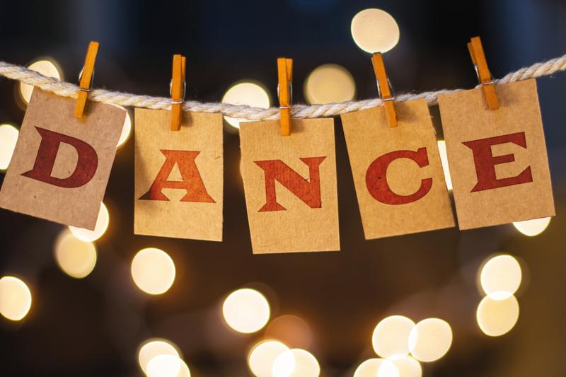 The word DANCE printed on clothespin clipped cards in front of defocused glowing lights.     Note  Visible grain at 100 , best at smaller sizes