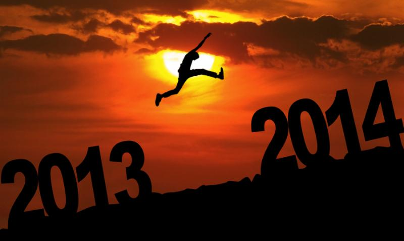 Silhouette of a man jumping from 2013 towards 2014 year at sunset