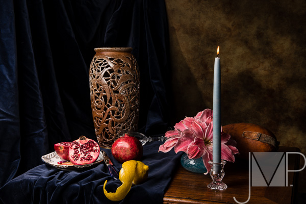 still life with candle, lemon and pomegranites