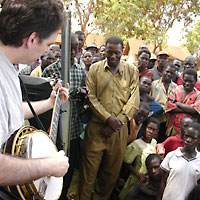 Bela Fleck playing his banjo to villagers