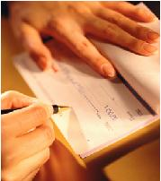 Picture of a person's hands writing a check.