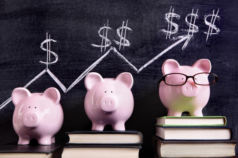 Three pink piggy banks standing on books next to a blackboard with simple savings progress chart. Sharp focus on the piggy banks.     Note  Shallow depth of field