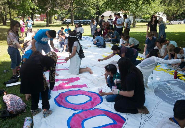 Leadership campers and Iraqi youth hard at work on the banner
