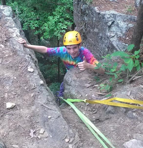 Boy climbing rocks at camp