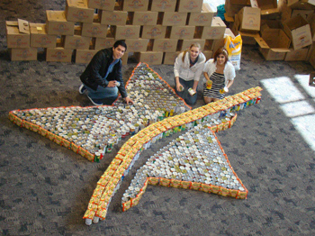 Students shape the campus logo with canned food and roman noodles