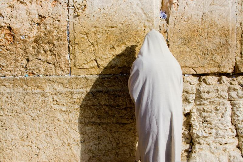 A religious orthodox Jew wearing a prayer shawl draped prays at the Wailing Wall. Jerusalem Israel.